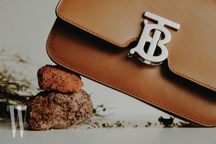 클래식하고 부드러운 광택이 특징인 버버리 TB백은 이탈리아산 카프 가죽을 사용했다. 미디엄, 스몰 두 가지 사이즈가 있으며, 크로스보디 또는 범 백 스타일로 출시된다. 사슴 다리 모양 귀고리와 TB 로고 귀고리는 모두 버버리 제품.