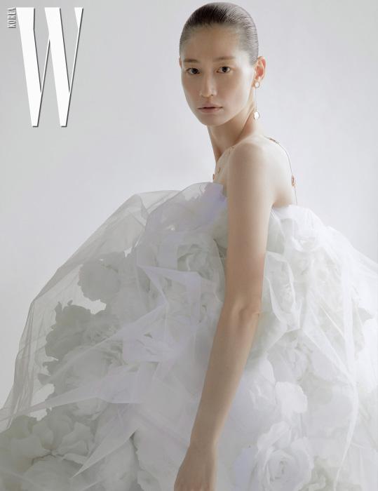 18K 핑크 골드에 화이트 자개와 다이아몬드가 세팅된 디사이드 귀고리, 네크리스 모두 Damiani 제품. 꽃 장식이 있는 드레스는 스타일리스트 소장품.