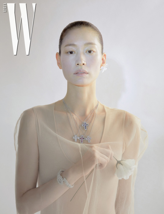 각각 다이아몬드, 루비, 사파이어가 세팅된 18K 화이트 골드 벨에포크 네크리스, 라운드 컷 다이아몬드 총 14.99캐럿이 세팅된 18K 화이트 골드 미모사 워치는 모두 Damiani 제품. 스킨톤의 슬리브리스 톱은 스타일리스트 소장품.