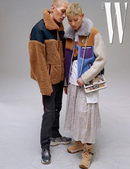 노마가 입은 멀티 컬러 재킷, 가죽 팬츠와 메탈릭 프린지 스니커즈는 모두 Coach 1941 제품. 수민이 입은 멀티 컬러 패치 재킷, 프린트 티셔츠, 꽃무늬 스커트, 스웨이드 부츠와 다양한 가죽으로 누빈 백은 모두 Coach 1941 제품.