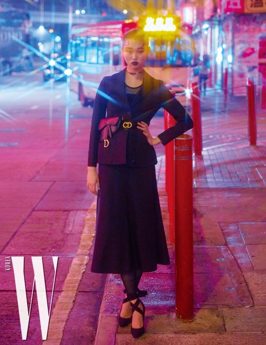 세련된 검정 슈트 재킷과 플레어 스커트, 안에 입은 망사 보디슈트, 가죽 벨트백, 스트랩 힐은 모두 Dior 제품.
