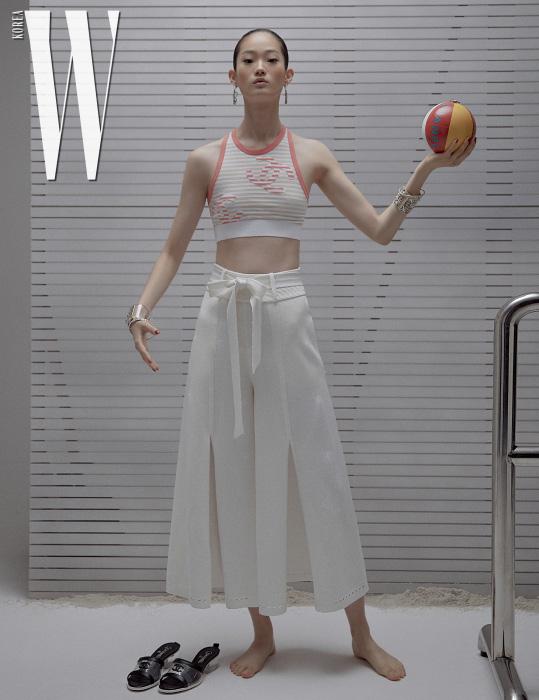 홀터넥 크롭트 톱과 슬릿 와이드 팬츠, 후프 귀고리, 슬라이드, 손에 든 비치볼 형태의 가방은 모두 Chanel 제품.