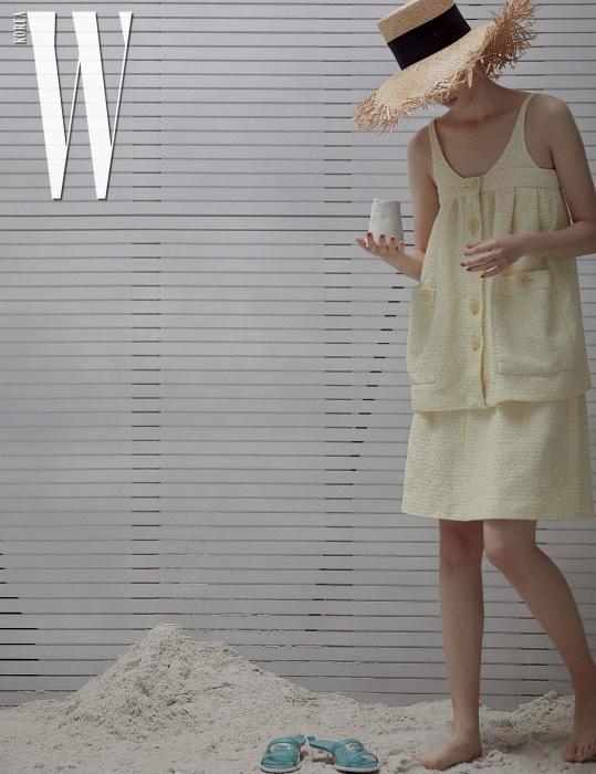 A라인 실루엣의 트위드 톱과 스커트, 밀짚모자, 슬라이드는 모두 Chanel 제품.