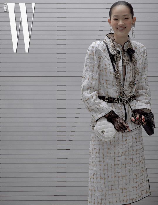 트위드 재킷과 스커트, 벨트, 양쪽으로 메는 형태의 핸드백과 메탈 네크리스, 로고 귀고리는 모두 Chanel 제품. 레이스 장갑은 에디터 소장품.