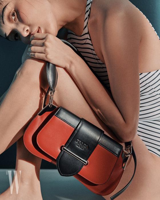붉은색과 검은색의 대비와 유연한 형태가 특징인 시도니 백은 프라다 제품. 3백 66만원. 줄무늬 원피스 수영복은 데이즈 데이즈 제품. 12만9천원.
