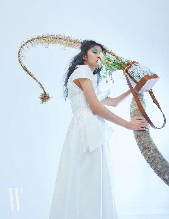 조형적인 화이트 드레스와 FF 로고 장식의 몬트레조 백, 꽃 장식 이어커프는 모두 Fendi 제품.
