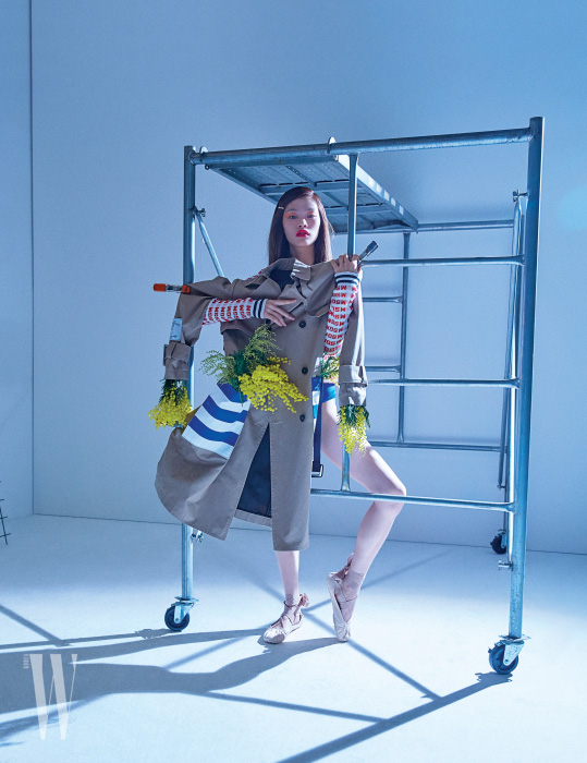 그래픽적인 줄무늬로 모던한 악센트를 더한 트렌치코트와 브랜드 로고 프린트 톱은 MSGM, 푸른색 브리프는 Cos, 누드 톤의 레이스업 발레리나 슈즈는 Dior 제품.
