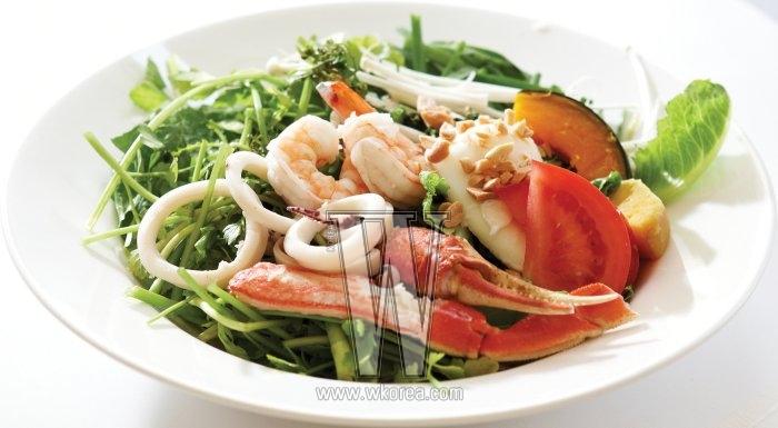향긋한 봄나물과 싱싱한 해산물의 맛을 한입에 누리고 싶다면 '해산물 봄나물 샐러드' 가 제격이다. 상큼한 생강 간장 소스는 재료들이 각각의풍미를 잃지 않으면서도 조화롭게 어우러지도록 돕는다.