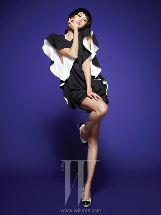 어깨의 풍성한 러플 장식, 검은색 겉감과흰색 안감이 그래픽적인 대조를 이루는미니 드레스, 검정과 흰색의 투 톤펌프스는 모두 Andy & Debb 제품.
