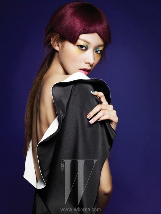 앞은 러플 장식의 하이네크라인으로, 등은 V라인으로깊게 파인 반전 드레스는Andy & Debb 제품.