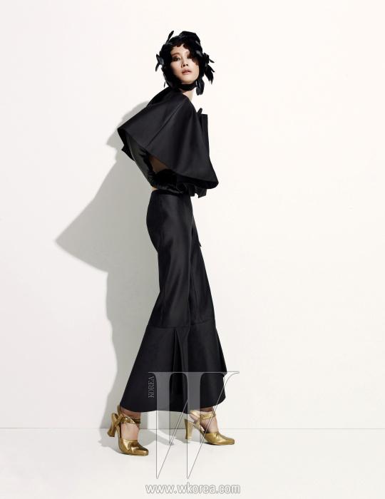 구조적이면서 언밸런스한 라인의 슬리브리스톱과 팬츠, 검정 가죽 소재의 긴 장갑,골드 색상의 슈즈, 깃털 장식의 헤드피스는모두 Miss Gee Collection 제품.