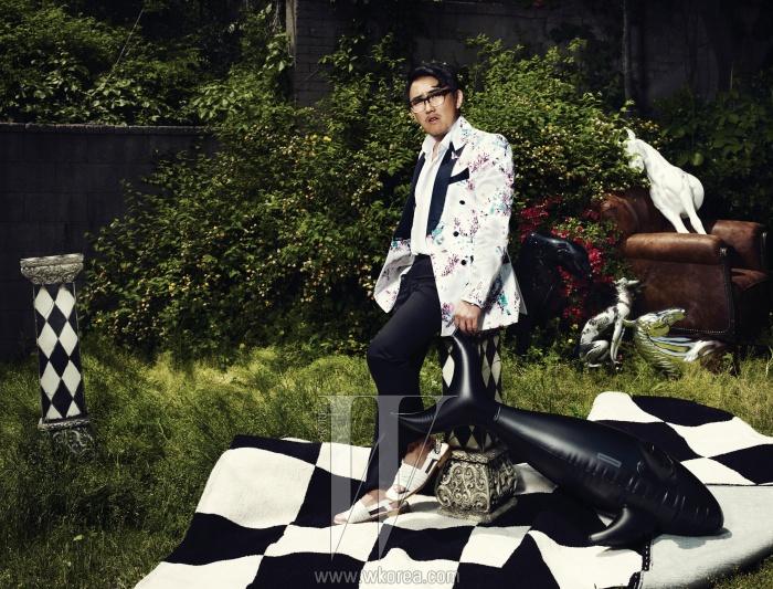 화려한 무늬의 턱시도 재킷은 Studio The Suit,흰색 핀턱 셔츠는 Kwon Oh Soo Classic,검정 바지는 Studio The Suit,흰색 샌들은 Songzio Homme,안경은 Retro Super Future By Modpop,튜브 돌고래는 Alexander Wang 제품.