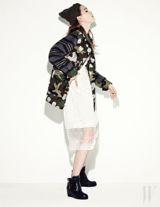카무플라주와 줄무늬가 린트된 재킷, 카키색 니트 비니, 아이보리색 레이스 드레스, 버클 장식 검정 부츠는 Steve J & Yoni P 제품.