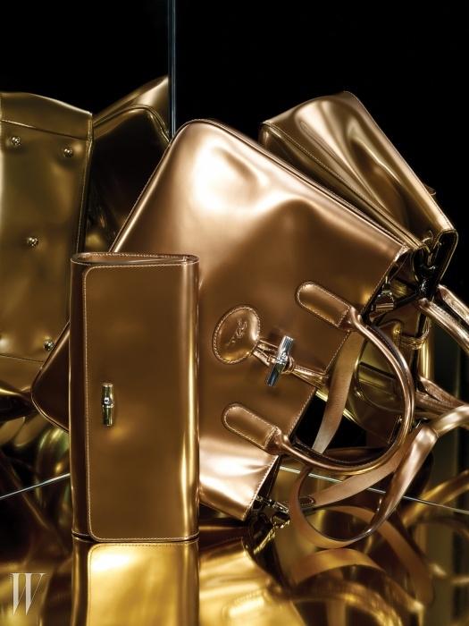 롱샴의 아이코닉 라인에 글로시함을 더한 로조 박스(Roseau Box) 컬렉션의 플래티넘 색상 토트백, 대나무 형태의 잠금 장식이 특징인 페이턴트 가죽 클러치는 모두 Longchamp 제품.