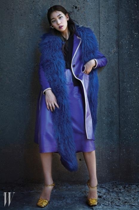 블라우스와 보라색 가죽 스커트, 라이닝이 돋보이는 가죽 코트, 풍성한 퍼 스톨, 이그조틱 가죽 소재의 앵클 스트랩 샌들은 모두 프라다, 이어커프는 엘리오나 제품.