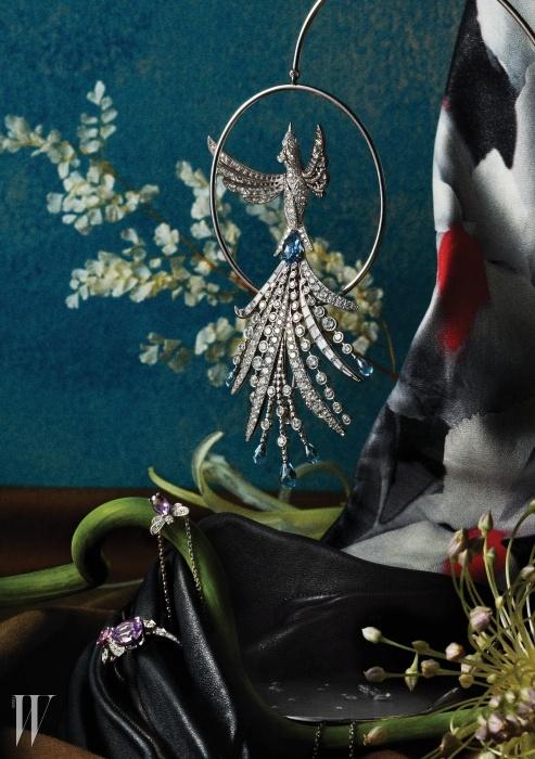 하늘에서 떨어진 운석 조각을 받침으로 사용했으며, 화이트 골드 소재에 투명한 아쿠아마린과 다이아몬드를 정교하게 세팅해 '달의 공작새'를 표현한 브로치 세트는 팡 드 륀(Paon de Lune) 컬렉션으로 Boucheron, 꽃을 표현한 아티스틱한 페인팅이 돋보이는 긴 가죽 장갑은 Dior, 벌의 몸통에 동그란 카보숑 컷 자수정이 세팅된 아트랩무아 비 애미시스트(Attrape-moi Bee Amethyst) 펜던트 목걸이는 Chaumet, 18K 화이트 골드 소재에 핑크 사파이어와 자수정을 세팅한 꿀벌 모티프의 비 마이 러브 퍼플 부틴(Bee My Love Purpel Butine) 반지는 Chaumet 제품.