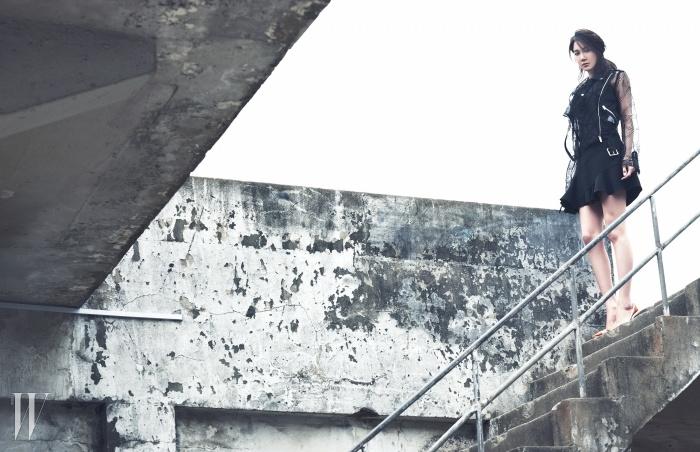 펀칭 디테일의 시스루 라이더 재킷은 Christopher Kane by Mue, 헴 라인의 러플 장식이 돋보이는 검정 원피스는 Victoria Beckham by Mue, 스틸레토 힐은 Dior 제품.