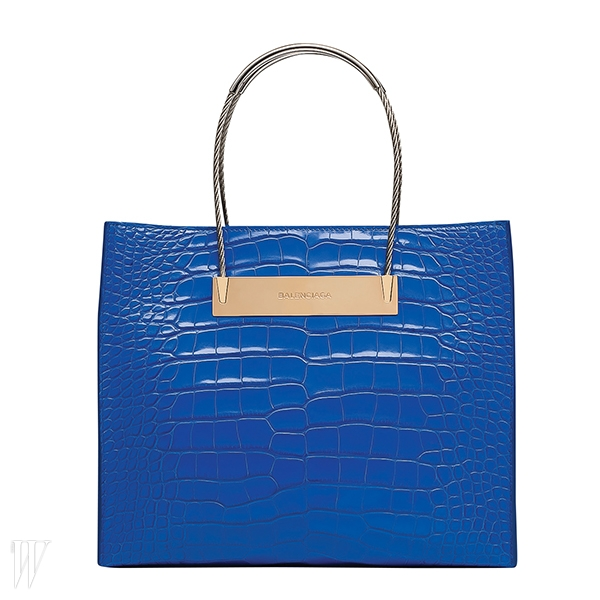 케이블 손잡이와 메탈 소재 로고판이 돋보이는 컬러풀한 가방은 발렌시아가 제품