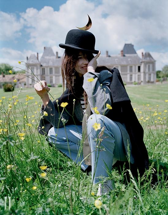 케이프는 Celine, 셔츠와 재킷은Charlotte Gainsbourg for Current/Eliott,파자마 팬츠는 Brooks Brothers,슈즈는 Adidas Originals,모자는 Christys' Hats London 제품.