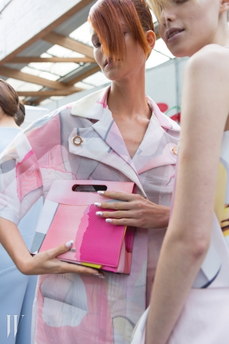 겐조 쇼에서 투명한 오간자소재 코트와 수채화처럼아름답게 물든 클러치를 든모델 이리나 크라첸코.