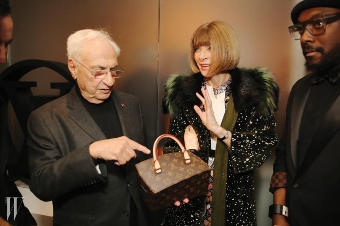 안나 윈투어에게 자신이 디자인한가방을 보여주는 건축가 프랭크 게리.