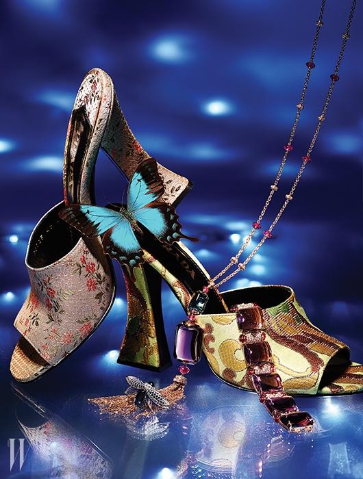 독창적이고 고풍스러운 우아함을 지닌자카드 소재의 꽃무늬 뮬은 둘 다 Prada,핑크 골드에 자수정과 루벨라이트 등유색석의 대담하고 풍성한 색감을 더한무사 컬렉션의 긴 목걸이와 팔찌는 Bulgari,영원한 사랑의 정수를 담은 채부활과 보호를 상징하는 풍뎅이 모양의케프리 사파이어 반지는 Boucheron 제품.