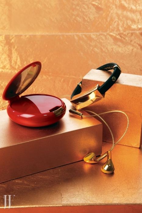 왼쪽   마이클 코어스의 휴대용 폰 충전기.오른쪽   레베카 밍코프의 가죽과 브라스 소재팔찌로 USB 케이블을 연결해 폰을 충전하거나데이터를 동기화할 수 있다. 아래는 해피플러그(Happy Plug)의 금빛 플라스틱 이어폰.
