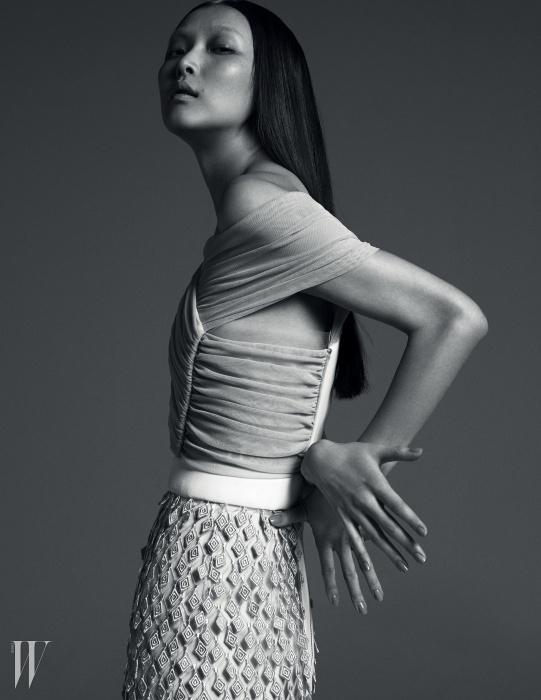다이아몬드 자수 조각이입체적으로 메시 튤 소재 위에아플리케된 관능적인 슬리브리스드레스는 Balenciaga 제품.