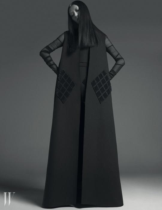 포켓 부분에 다이아몬드 패턴의엠브로이더리 자수가 장식된트라페즈 라인의 맥시 코트,안에 입은 검은색 메시 소재의 톱과쇼츠는 모두 Balenciaga 제품.