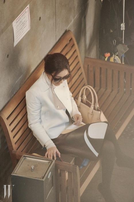 크림색 가죽 라이더 재킷과 스커트, 정갈한 디자인의 캐멀 색상 케이프 백은 모두 토즈 제품.