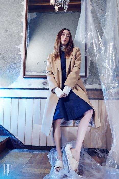 날 선 테일러링의 캐멀색 코트,레터링 자수를 더한 드레스, 부드러운 색감의터틀넥 스웨터, 가죽과 퍼 소재가 믹스된슬리퍼는 모두 The Studio K 제품.