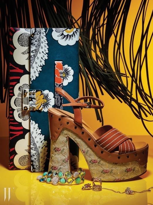 화려한 색감과 그래픽적인 꽃무늬가돋보이는 가죽 클러치는 Valentino,잔잔한 꽃무늬 자수 장식의 패브릭 굽이 빈티지한매력을 자아내는 플랫폼 샌들은 Prada,로즈 골드로 둘러싸인 동그란 크리소프레이즈원석과 푸른색 토파즈가관능적이며 화려한매력을 발산하는 벨 리브 컬렉션의 팔찌는 Fred,핑크 골드에 보랏빛 자수정과 다이아몬드가장식된 로즈 디올 프리 카텔란 컬렉션의 장미펜던트 목걸이,아카이브의 카나주 패턴에서 영감을받은 조형적인 형태의옐로 골드와 핑크 골드 소재마이 디올 반지는 모두 Dior Fine Jewelry,독창적인 사쿠라 골드 소재에 오묘한 빛을발하는세 가지 색상의 가넷을 세팅한 나뭇잎모티프의 비잔틴 컬렉션 반지는 Tasaki 제품.