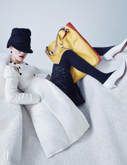 모던한 디자인의 패딩 코트와 검정 퀼팅 스커트, 클래식한 키튼힐 슈즈와 컬러 블록이 돋보이는 숄더 백은 모두 Celine, 검은색 니트 모자는 Kenzo 제품.