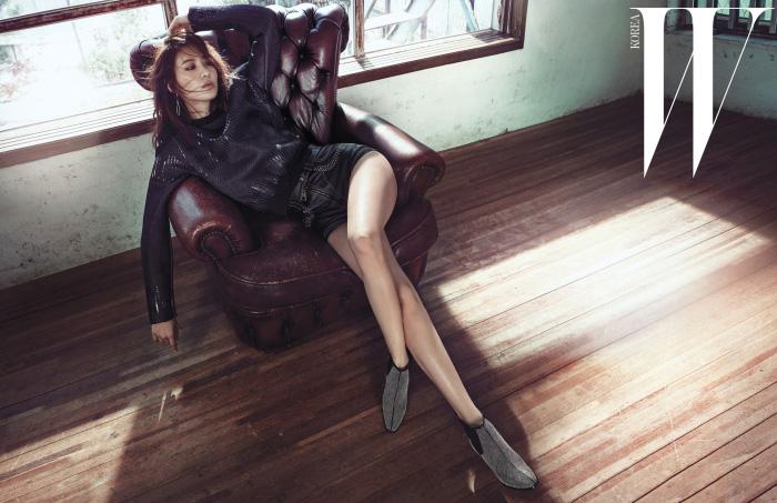 구조적인 실루엣의 검정 스웨트셔츠와 가죽 소재 쇼트 팬츠는 Louis Vuitton, 길게 늘어지는 드라마틱한 실버 귀고리는 Dior, 금색 스터드 장식의 화려한 첼시 부츠는 Roger Vivier 제품.