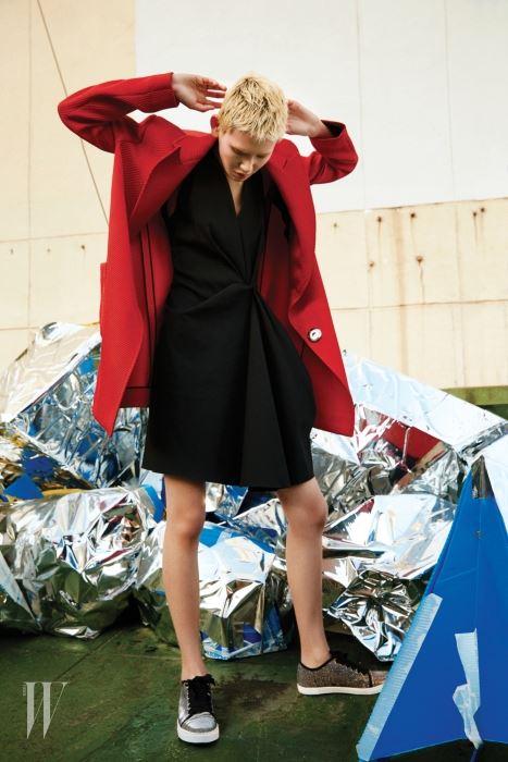 강렬한 빨간색 트윌 조직 코트와 보 장식 검정 드레스, 글리터 소재 스니커즈는 모두 Lanvin 제품.