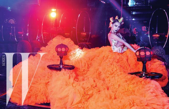 거대한 볼륨의 주황색 튤 스커트와 자수 장식 톱은 Giambattista Valli Couture 제품.
