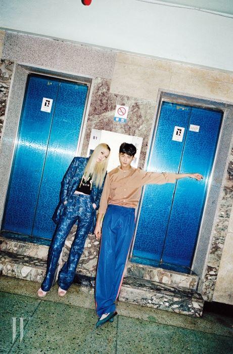 장수임이 착용한 푸른색 카무플라주 패턴의 팬츠 슈트와 크롭트 톱, 슈즈는 모두 Jain Song, 체인 장식을 늘어뜨려 연출하는 황금빛 초커형 목걸이는 Tany by Minetani 제품.  변우석이 착용한 셔츠와 팬츠는 모두 Heich Es Heich, 슈즈는 Acrobat 제품.