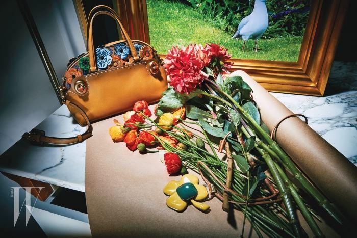 향기의 조각 가죽 플라워 아플리케가 장식된 클래식한 사첼백은 코치 제품. 1백만원대, 추상적인 형태의 꽃 모양 목걸이는 마르니 제품. 가격 미정.