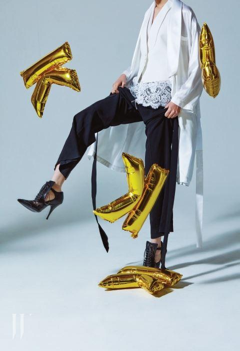 안에 입은 하얀색 레이스 톱, 하얀색 테일러드 베스트, 위에 입은 실크 롱 재킷, 기다란 끈이 장식된 검정 팬츠, 코르셋을 연상시키는 검은 부티는 모두 지방시 by 리카르도 티시 제품. 가격 미정.
