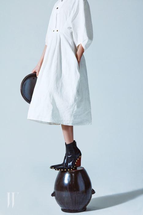 둥근 볼륨이 돋보이는 마 소재 드레스, 웨스턴 부츠의 형태를 닮은 나무 굽의 앵클부츠는 셀린 제품. 가격 미정.