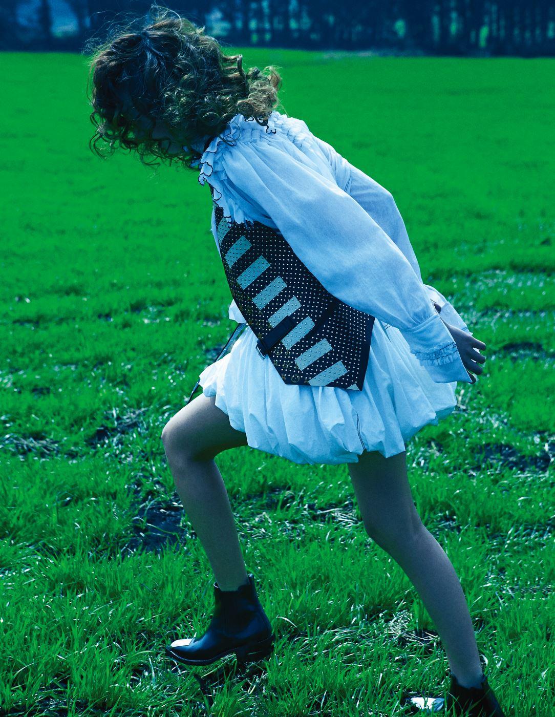 러플 장식의 풍성한 벌룬 드레스, 모노그램 패턴의 가죽 베스트, 메탈 포인트 앵클부츠는 모두 Louis Vuitton 제품.