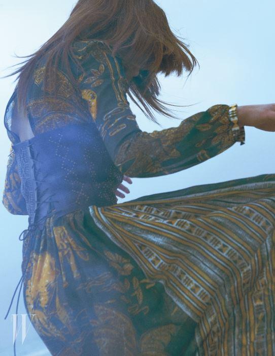 아프리칸 프린트의 에스닉 드레스, 가죽 코르셋은 Valentino 제품.