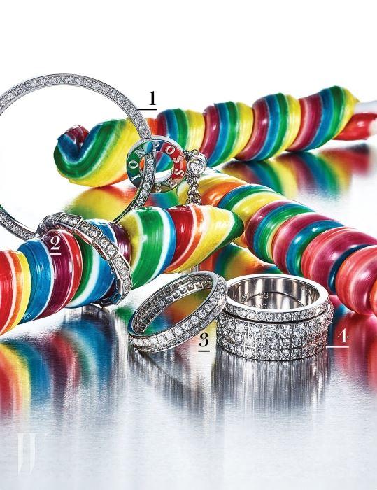 1. 자유롭게 회전하는 '링 안의 링'이라는 콘셉트가 독창적이며 체인의 길이를 조절해 다양한 연출이 가능한, 화이트 골드 소재에 다이아몬드가 풀 파베 세팅된 포제션 유&미 목걸이는 Piaget 제품. 2. 풍요, 지혜, 불멸과 장수를 상징하는 뱀으로부터 영감을 받아 독자적인 장인 기술과 디자인으로 정교하게 재해석한 화이트 골드와 다이아몬드 소재의 세르펜티 웨딩 밴드는 Bulgari 제품. 3. 유연하게 날이 선 조형적인 형태가 우아하게 돋보이는, 다이아몬드 세팅의 플래티넘 소재 쿠튀르 웨딩 밴드는 Van Cleef & Arpels 제품. 4. 떨어지지 않도록 대담하게 연결된 화이트 골드 소재의 두 개의 밴드가 서로의 주변을 자유롭게 움직이며, 반지의 곡선미와 스퀘어 세팅의 다이아몬드가 만들어내는 화려한 대비가 돋보이는 포제션 엑상트리크 밴드형 반지는 Piaget 제품.