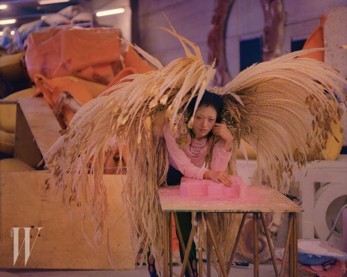분홍색 크롭트 톱은 Elisa Biroli, 멀티 컬러의 비즈 장식과 컷오프의 튤 장식 검정 레깅스는 Augustin Teboul, 푸른색 앵클부츠는 Marios 제품. 날개 장식은 삼바 학교(Samba School) 협찬 제품.