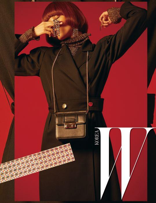 80년대풍의 파워숄더 롱 코트, 반짝이는 라메 소재의 톱, 폭포처럼 쏟아지는 크리스털 이어링, 미니멀한 디자인의 체인 스트랩 지지(Jiji) 백은 모두 Lanvin 제품.