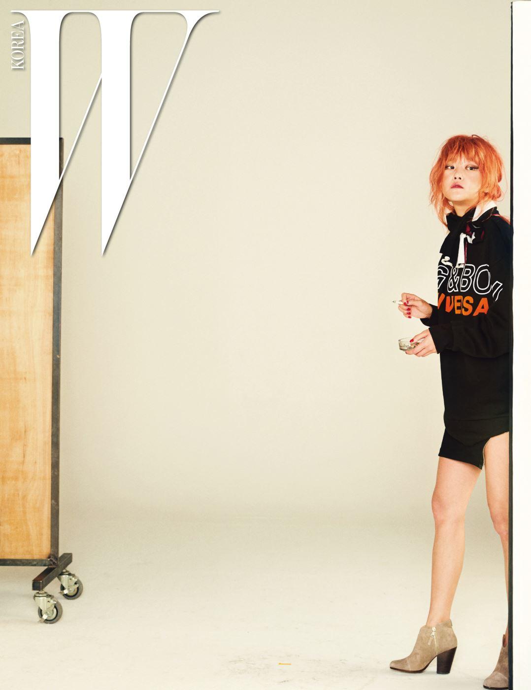 흰색과 오렌지색 그래픽 로고가 돋보이는 큼직한 모토 풀오버, 사선 지퍼 장식 스커트, 옅은 회색 부티, 머플러처럼 돌려 감은 검정과 하양 배색 스웨터는 모두 Rag&Bone 제품.