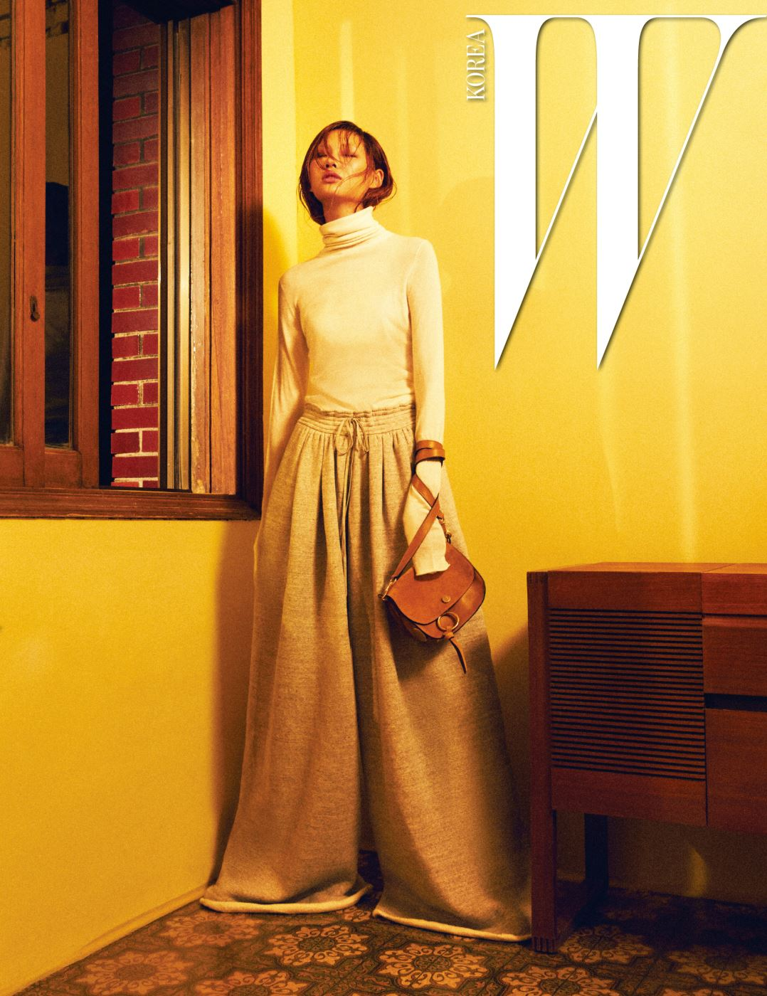 피부가 살짝 비칠 정도로 얇은 아이보리색 터틀넥 톱, 밑단이 드라마틱하게 넓어지는 트랙 팬츠, 캐멀색 커티스 스트랩 백은 모두 Chloe 제품.