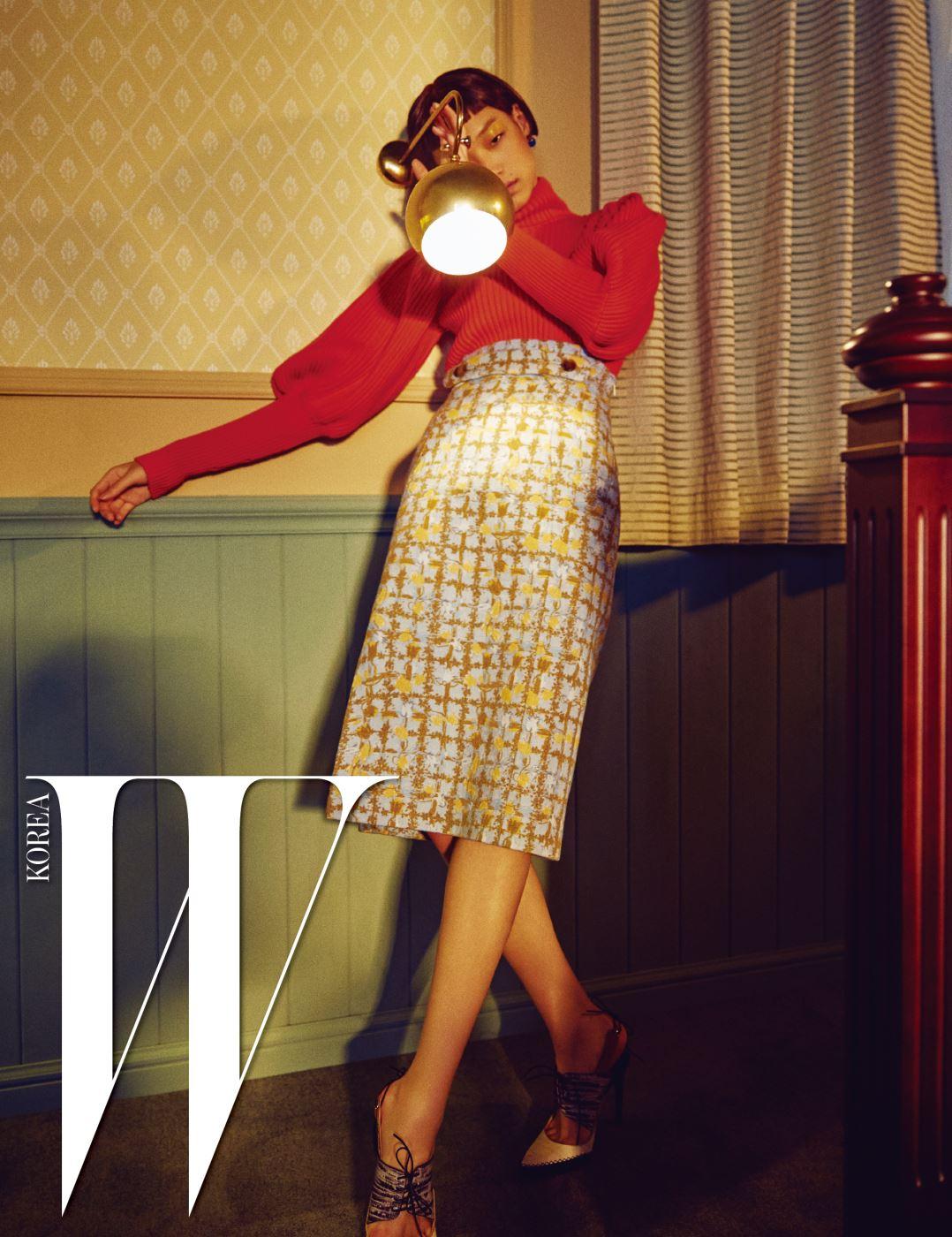 퍼프 소매 터틀넥 니트 톱, 허리선이 높은 스커트, 레이스업 슬링백 펌프스, 이어링과 드롭 이어커프, 레이어드한 링은 모두 Dior 제품. 침대 프레임은 SIMMONS Collectionon 벨로Ⅱ제품.