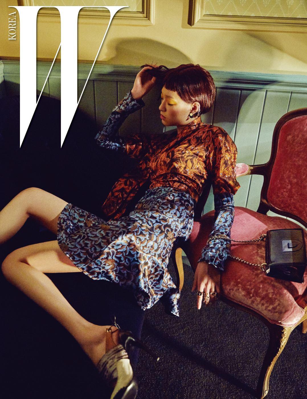 식물 모티프 패턴의 실크 미니 드레스, 레이스업 슬링백 펌프스, 체인 스트랩의 미니 백, 이어링과 드롭 이어커프, 레이어드한 링은 모두 Dior 제품.
