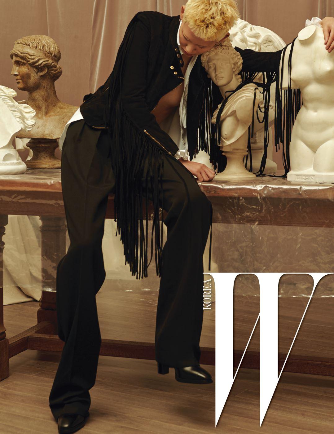 소매의 러플이 포인트인 셔츠, 말의 갈기를 연상시키는 프린지 스웨이드 재킷, 검은색 통 넓은 팬츠, 검정 앵클부츠는 모두 Ralph Lauren Collection 제품.